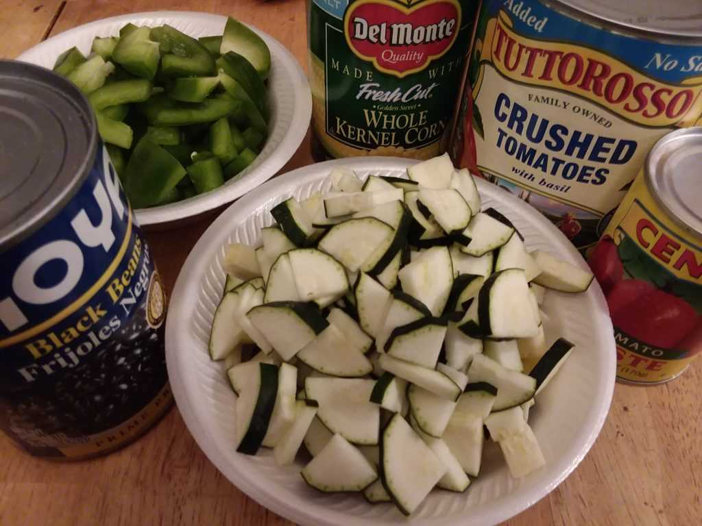 Ingredients for Chamoy Chicken Chili arranged on a table. Black beans, green peppers, canned corn, canned crushed tomatoes and zucchini