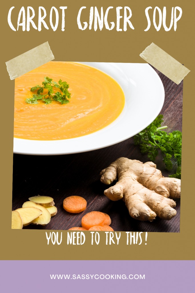 Ginger Carrot Soup in a white bowl with sliced carrots and fresh ginger surrounding it on a dark wood table.